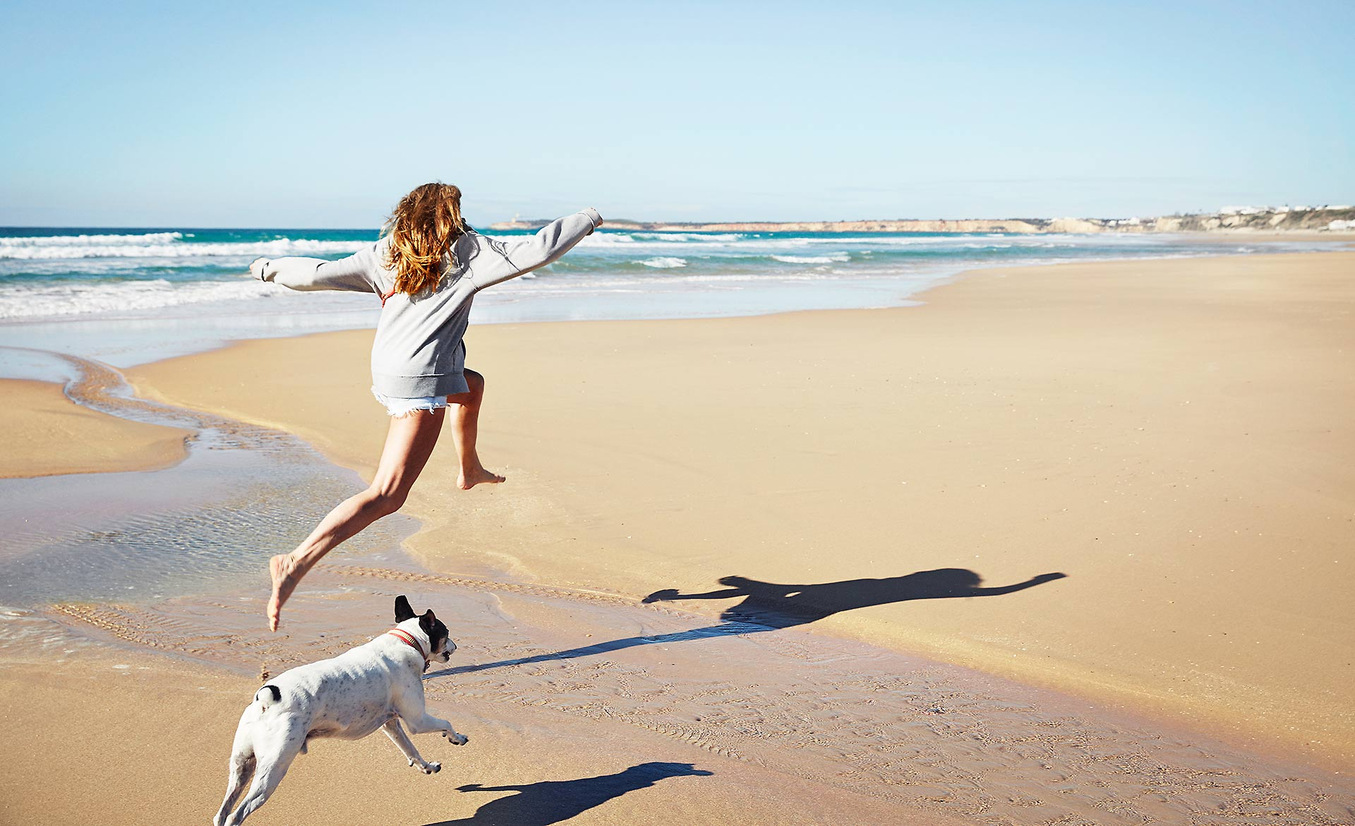 Women leaping with dog
